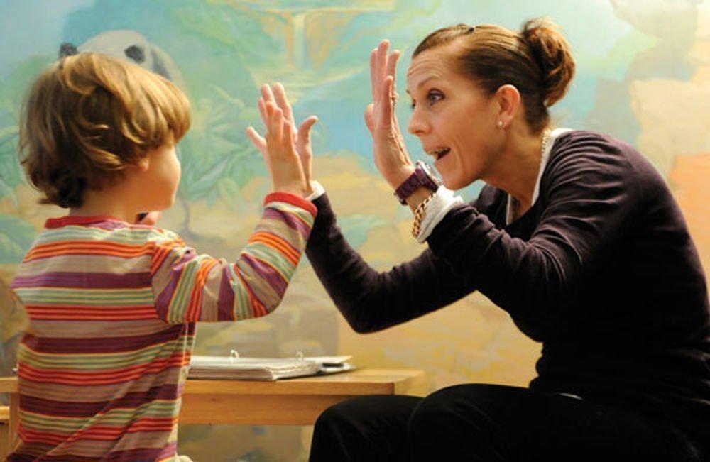 Un bambino e una maestra che giocano insieme, battendosi un cinque
