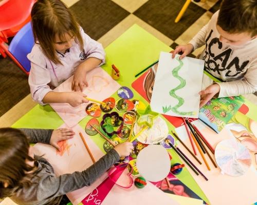 Bambini che svolgono un'attività di gruppo inclusiva, colorando insieme su dei fogli
